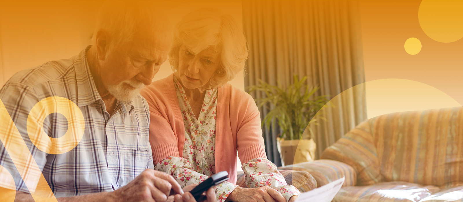 An image of an elderly couple, in their living room, looking at their finances.